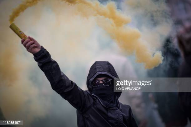A protester waves a smoke generator during a demonstration marking the first anniversary of the yellow vest movement on November 16 in Nantes western...