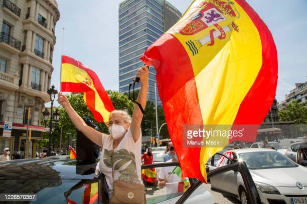 Protester waves a Spanish flag from her car on May 23, 2020 in Barcelona, Spain. The far-right political party Vox has called for demonstrations in...