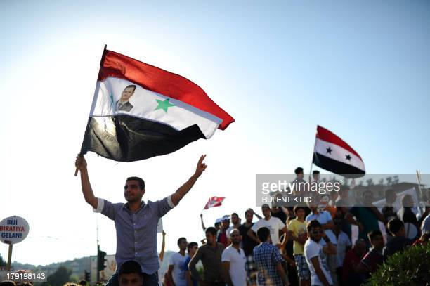 A protester waves a Syrian flag with the photograph of Syrian President Bashar alAssad during a rally against a possible attack on Syria in response...