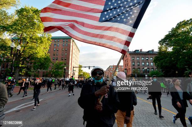A protester waves a US flag as people march during a demonstration over the death of George Floyd an unarmed black man who died in Minneapolis Police...
