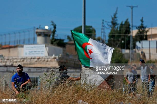 A protester waves an Algerian flag during a demonstration near the Jewish settlement of Beit El near Ramallah in the occupied West Bank June 29 2018