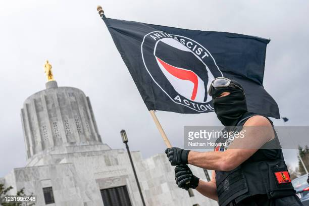 Protester waves an anti-fascist flag at the Oregon statehouse on March 28, 2021 in Salem, Oregon. The protesters clashed with occupants of vehicles...