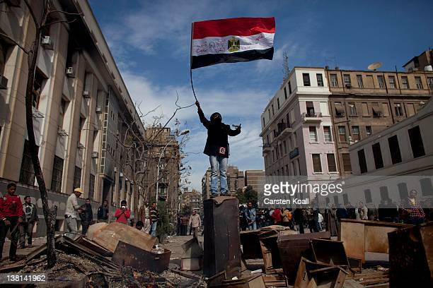 A protester waves an Egyptian flag on the top of a barrier during clashes between protesters and riot police near the interior ministry February 3...