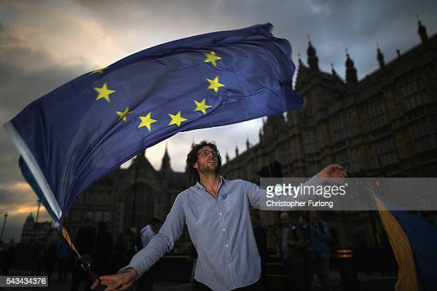 A protester waves an EU flag in front of the Houses of Parliament as they demonstrate against the EU referendum result on June 28 2016 in London...