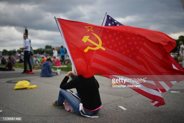 Protester waves flags of the Soviet Union and of the USA prior to a demonstration against lockdown measures and government policy during the...