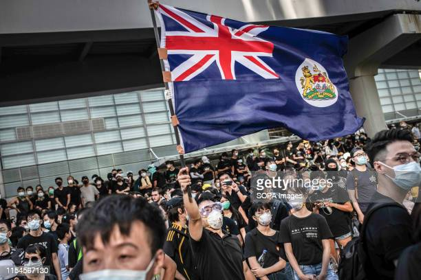 Protester waves Hong Kong colonial flag in the middle of crowd in front of Hong Kong Legislative Council building during demonstration against the...