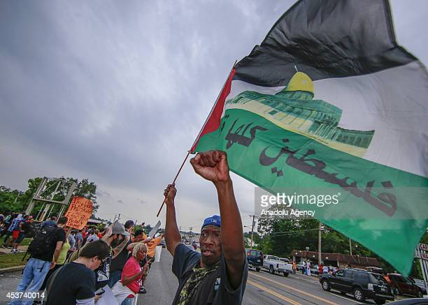 A protester waves Palestinian flag in solidarity with Gaza as Americans shout slogans and hold banners during a demonstration against the death of...