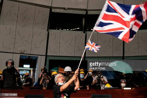 A protester waves the British Union Jack flag in the parliament chamber after they broke into the government headquarters in Hong Kong on July 1 on...