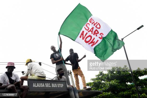 Protester waves the Nigerian national flag while gathering with other protesters to barricade the Lagos - Ibadan expressway, the oldest highway and...