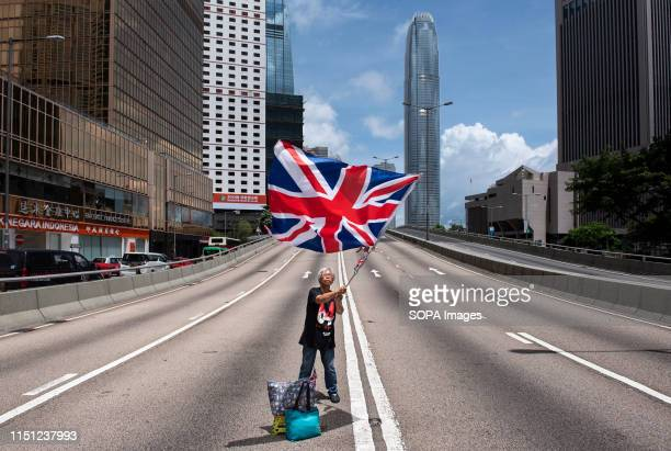 A protester waves the United Kingdom of Great Britain and Northern Ireland flag after roads have been blocked by the protesters Despite the Chief...