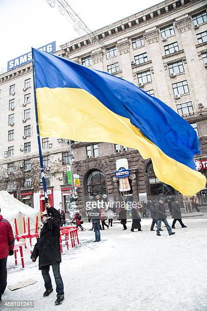 A protester waving a huge flag of Ukraine near the Maidan Square on December 11 2013 in Kiev Ukraine Thousands have been protesting against the...