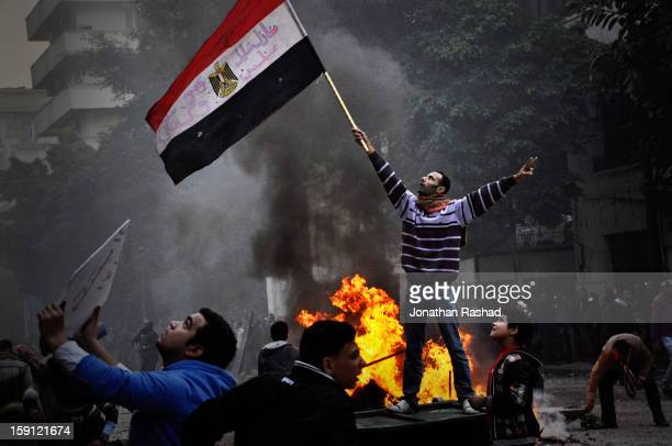 Protester waving the Egyptian flag as the army soldiers throw rocks at protesters from a rooftop that overlooks the Qasr Ainy street, off Tahrir...