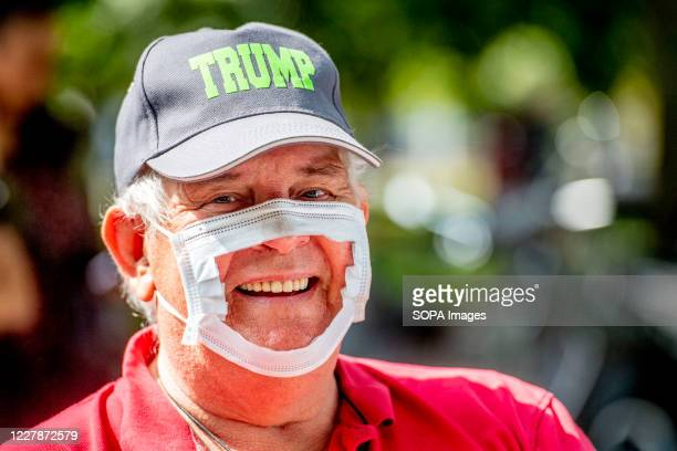 Protester wearing a broken mask and a Trump cap during the demonstration. The Virus Madness action group organised a demonstration at Malieveld...