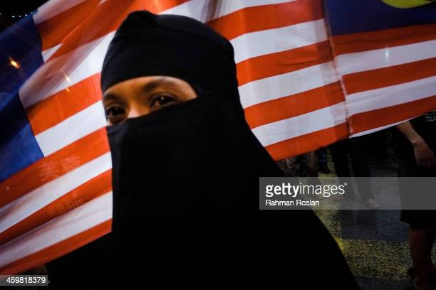 A protester wearing a burqa walks past a Malaysian flag during a protest against price hikes by the Malaysian Government on December 31 2013 in Kuala...