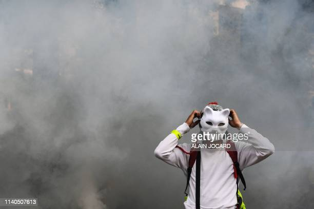 A protester wearing a cat mask stands in front of tear gas smoke during clashes on the sidelines of the annual May Day rally in Paris on May 1 2019...