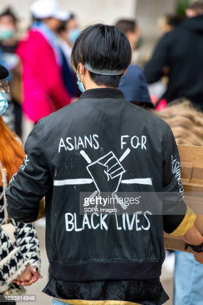 Protester wearing a coat with 'Asians for black lives 'written on it during a Stop Asian Hate protest at Parliament Square in London. Anti-Asian...