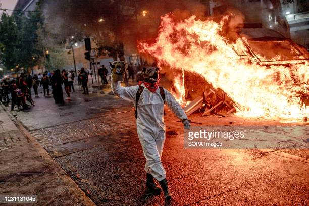 Protester wearing a dog head costume walks past the burning flames of a police vehicle during a protest against police brutality in Santiago. Several...