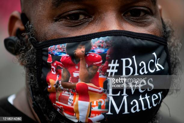Protester, wearing a face mask featuring Colin Kaepernick kneeling, joins a protest in Washington, DC, against racism and police brutality, on June...