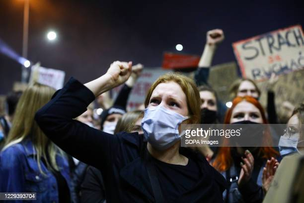 Protester wearing a face mask hold up her fist during the demonstration. The Polish Constitutional Court in its new, politically chosen courthouse...