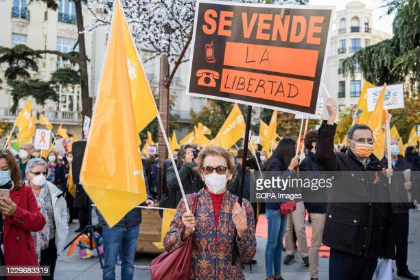 Protester wearing a face mask holds a placard during a demonstration. Dozens of people demonstrate in front of the Spanish Congress of Deputies,...