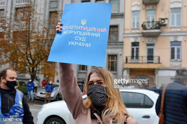 Protester wearing a face mask holds a placard expressing her opinion outside the Constitutional Court building during the demonstration. Hundreds of...