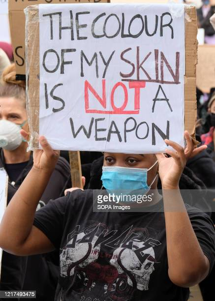 Protester wearing a face mask holds a placard saying the colour of my skin is not a weapon during a peaceful demonstration. Protesters gathered at...