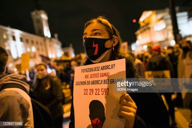 Protester wearing a face mask holds a placard with a phone number for abortion information during the demonstration. Tens of thousands of people took...