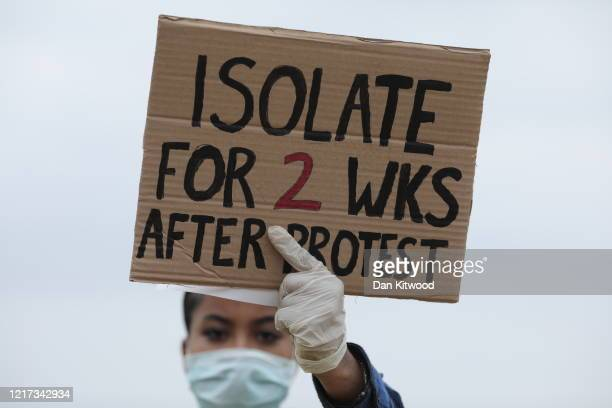 A protester wearing a face mask holds up a sign saying 'Isolate for 2 weeks after protest' during a Black Lives Matter protest in Hyde Park on June 3...