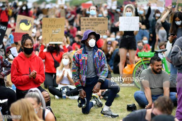 Protester wearing a face mask kneels during a Black Lives Matter protest in Hyde Park on June 3, 2020 in London, United Kingdom. The death of an...