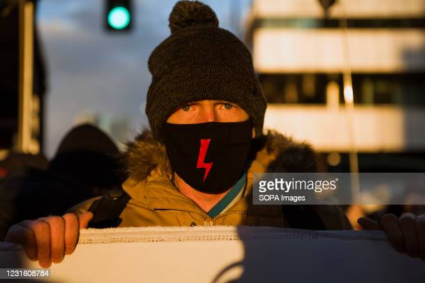 Protester wearing a face mask painted with a red bolt - the symbol of Women's Strike takes part during the demonstration. People took the streets in...