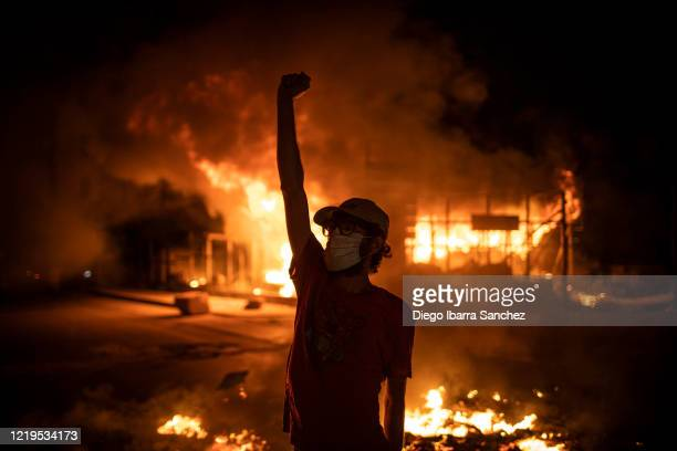 Protester wearing a face mask raises his fist in front of a burning building as large-scale protests resume on June 11, 2020 in Beirut, Lebanon. The...