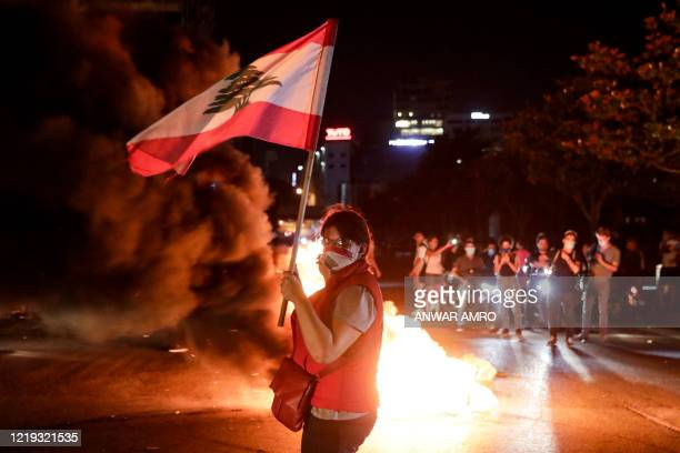 Protester wearing a face mask showing the Lebanese national flag stands holding a national flag near flaming tires during a demonstration against...