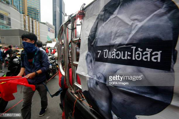 Protester wearing a face mask, walks past a picture of the Thailand's Prime Minister Prayuth Chan O-Cha during a car mob demonstration. More than...