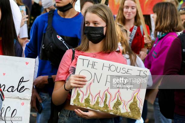 A protester wearing a face mask while holding a placard during the march in London Hundreds of young people worldwide joined hands in the third such...