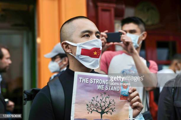 Protester wearing a face mask with a Chinese flag printed on it takes part during the demonstration. Hongkongers held demonstrations in ten different...