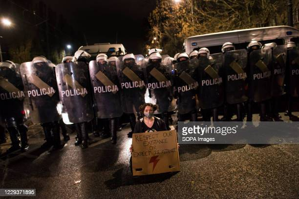 Protester wearing a face mask with a placard sits in front of the riot police forces guarding Kaczynski's house during the demonstration. Tens of...