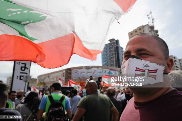 Protester wearing a face mask with an illustration depicting a raised fist before a Lebanese flag looks on as he attends a demonstration against...