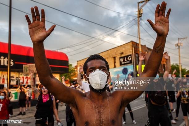 TOPSHOT A protester wearing a facemask holds up his hands during a demonstration over the killing of George Floyd by a policeman outside the Third...