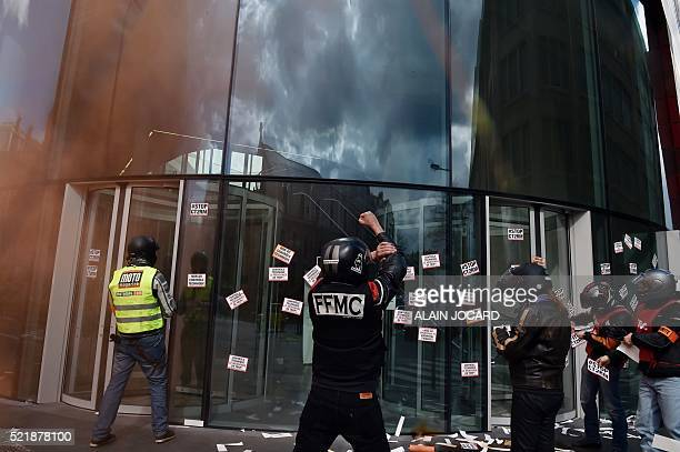 A protester wearing a 'Federation Francaise des Motards en Colere' vest puts stickers on a window at an annex of the Interior Ministry in Paris on...