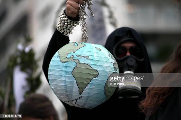 A protester wearing a gas mask holding an earth shaped lantern during protest rally by environmental and political organisations in front of the...