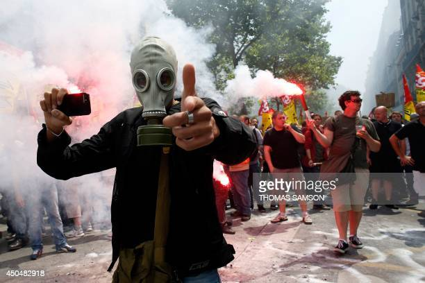 A protester wearing a gas mask holds a smartphone and gestures during a demonstration by striking employees of the French state rail company SNCF...