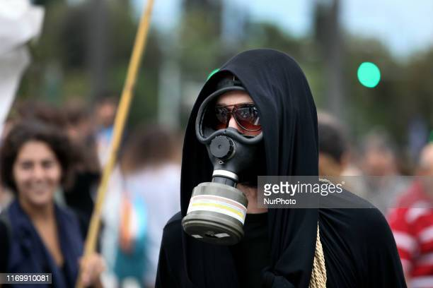 A protester wearing a gas mask is seen during protest rally by environmental and political organisations in front of the Greek Parliament during...