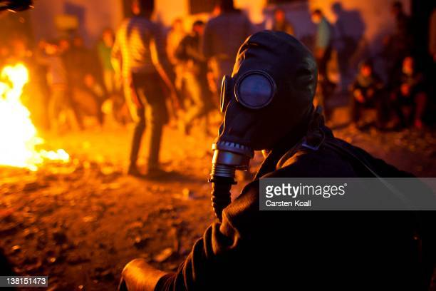 A protester wearing a gas mask sits close to a fire as protests near to Egypt's Interior Ministry continued for a second consecutive day on February...