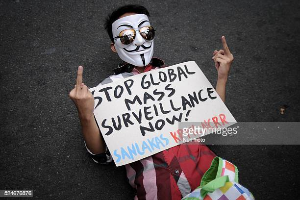 A protester wearing a Guy Fawkes mask gestures as he lies on the road during a demonstration to mark the global 'The Day We Fight Back' protest...