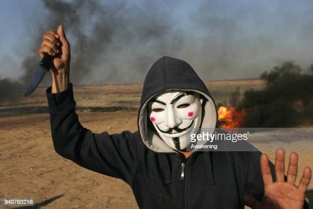 A protester wearing a Guy Fawkes mask holds a knife during clashes with Israeli security forces following a demonstration near the border with Israel...