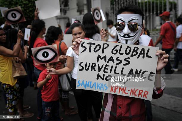 A protester wearing a Guy Fawkes mask holds up a placard during a demonstration to mark the global 'The Day We Fight Back' protest against mass...