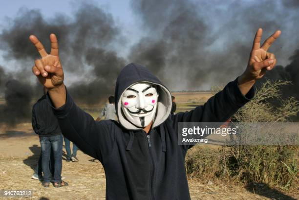 A protester wearing a Guy Fawkes mask makes the sign of victory during clashes with Israeli security forces following a demonstration near the border...