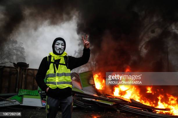 Protester wearing a Guy Fawkes mask makes the victory sign near a burning barricade during a protest of Yellow vests against rising oil prices and...