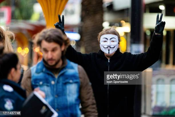 A protester wearing a Guy Fawkes mask stands against the current Coronavirus lockdown laws at Acland Street St Kilda during COVID19 on 01 May 2020 in...
