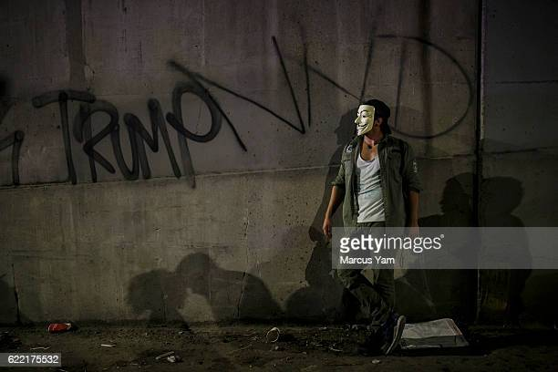 A protester wearing a Guy Fawkes mask stands aside watching other antiTrump protesters on the 101 freeway in Los Angeles Calif on Nov 10 2016